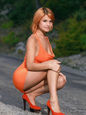 """Wearing a body-hugging dress that shows off her sexy curves and sexy orange pumps, Violla A turns an outdoor shoot to a naughty striptease."""